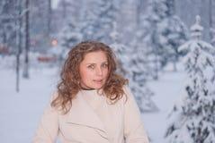 Χειμερινό πορτρέτο μιας γυναίκας στο άσπρο παλτό κατά τη διάρκεια των χιονοπτώσεων σε ένα πάρκο Στοκ φωτογραφίες με δικαίωμα ελεύθερης χρήσης