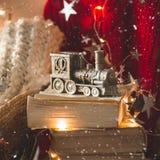 Χειμερινό πουλόβερ που τοποθετούνται σε μια καρέκλα με τα βιβλία και την ατμομηχανή, τραίνο των διακοσμήσεων Χριστουγέννων Κωνοφό στοκ εικόνα με δικαίωμα ελεύθερης χρήσης