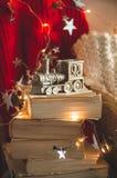 Χειμερινό πουλόβερ που τοποθετούνται σε μια καρέκλα με τα βιβλία και την ατμομηχανή, τραίνο των διακοσμήσεων Χριστουγέννων Κωνοφό στοκ εικόνες