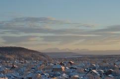 Χειμερινό προάστιο σε ένα υπόβαθρο των λόφων και των βουνών Στοκ Εικόνες