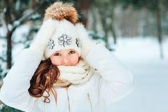Χειμερινό στενό επάνω πορτρέτο του χαριτωμένου ονειροπόλου κοριτσιού παιδιών στο άσπρα παλτό, το καπέλο και τα γάντια στοκ φωτογραφία