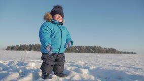 Χειμερινό στενό επάνω υπαίθριο πορτρέτο του λατρευτού ονειροπόλου αγοράκι, ευτυχές παιχνίδι αγοράκι στο χιόνι, υπαίθρια απόθεμα βίντεο