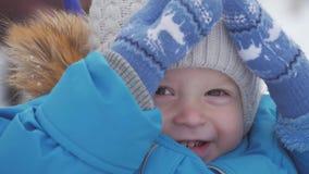 Χειμερινό στενό επάνω υπαίθριο πορτρέτο του λατρευτού ονειροπόλου αγοράκι, ευτυχές παιχνίδι αγοράκι στο χιόνι, υπαίθρια φιλμ μικρού μήκους