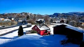 Χειμερινό τοπίο με τα χιονώδη σπίτια και βουνά με ένα κόκκινο σπίτι στο κέντρο και το σαφή μπλε ουρανό σε μια ηλιόλουστη ημέρα στοκ εικόνες