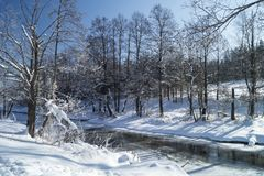 Χειμερινό τοπίο με τον ποταμό στο ξύλο με το χιόνι Στοκ φωτογραφία με δικαίωμα ελεύθερης χρήσης