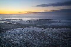 Χειμερινό τοπίο με το ηλιοβασίλεμα και την παγωμένη λίμνη στοκ εικόνα