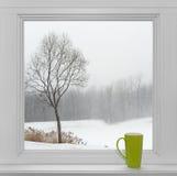 Χειμερινό τοπίο που βλέπει μέσω του παραθύρου και του πράσινου φλυτζανιού Στοκ φωτογραφία με δικαίωμα ελεύθερης χρήσης