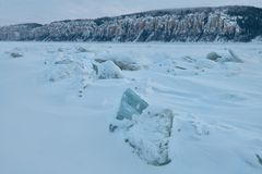 Χειμερινό τοπίο στους μπλε τόνους με το ridged πάγο στον παγωμένο ποταμό στο λυκόφως στοκ εικόνες