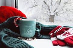 Χειμερινό υπόβαθρο - κοιλάνετε με τον κάλαμο καραμελών, το μάλλινα μαντίλι και τα γάντια στο windowsill και τη χειμερινή σκηνή υπ Στοκ Φωτογραφία