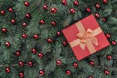 Χειμερινό υπόβαθρο των κλάδων έλατου Εξωραϊσμένος με τα κόκκινα μπιχλιμπίδια και το δώρο ουρανός santa του Klaus παγετού Χριστουγ στοκ φωτογραφία με δικαίωμα ελεύθερης χρήσης
