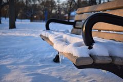 Χειμερινό χιόνι σε έναν πάγκο πάρκων στοκ εικόνες