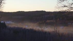 Χειμερινό χωριό στην ομίχλη στο ηλιοβασίλεμα απόθεμα βίντεο