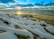 Χειμερινό seascape, πέτρες στο χιόνι και το ηλιοβασίλεμα ν Στοκ φωτογραφίες με δικαίωμα ελεύθερης χρήσης