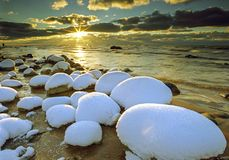 Χειμερινό seascape, πέτρες στο χιόνι και το ηλιοβασίλεμα ν Στοκ Εικόνες