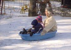 Χειμώνας γιαγιάδων & εγγονιών που γλιστρά κάτω από το λόφο στη λίμνη παιδάκι Στοκ Εικόνες