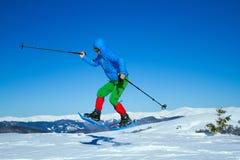 Χειμώνας που στα βουνά στα πλέγματα σχήματος ρακέτας με ένα σακίδιο πλάτης και μια σκηνή Στοκ εικόνα με δικαίωμα ελεύθερης χρήσης