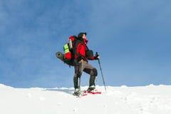 Χειμώνας που στα βουνά στα πλέγματα σχήματος ρακέτας με ένα σακίδιο πλάτης και μια σκηνή Στοκ Φωτογραφίες