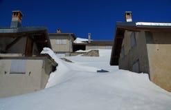 Χειμώνας-σταθερά σπίτια που εμποδίζονται από φρέσκα, ομαλά snowdrifts Στοκ Φωτογραφία
