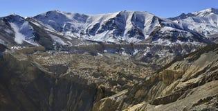 Χειμώνας στα βουνά: οι σειρές βουνών καλύπτονται με το χιόνι στις κορυφές, είναι κατωτέρω οι κίτρινοι και καφετιοί βράχοι, τα Ιμα Στοκ φωτογραφία με δικαίωμα ελεύθερης χρήσης