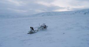 Χειμώνας στη Σιβηρία, ένα άτομο που φορά τη γούνα έχει έναν γύρο με τους ταράνδους στη μέση του τομέα 4K απόθεμα βίντεο