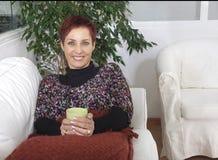 Χειμώνας στο σπίτι: τσάι κατανάλωσης γυναικών Στοκ Φωτογραφίες