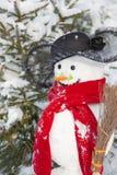 Χειμώνας - χιονάνθρωπος σε ένα χιονώδες τοπίο με ένα καπέλο και ένα κόκκινο μαντίλι Στοκ Φωτογραφία