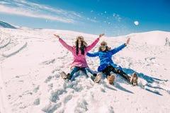Χειμώνας, δύο κορίτσια που έχει τη διασκέδαση στο χιόνι στα βουνά στοκ φωτογραφίες