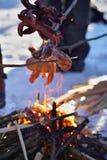 Χειμώνας cookout με τα λουκάνικα επάνω από την πυρκαγιά που τοποθετείται στο χιόνι Στοκ φωτογραφία με δικαίωμα ελεύθερης χρήσης
