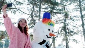 Χειμώνας selfie, χαριτωμένο κορίτσι που κάνει τη φωτογραφία με το χιονάνθρωπο, ένα κινητό τηλέφωνο στο χέρι της νέας γυναίκας που απόθεμα βίντεο