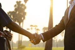 Χειραψία για να είναι μια σύμβαση σε συμφωνία Μεταξύ των επιχειρηματιών και των αγροτών στοκ εικόνες