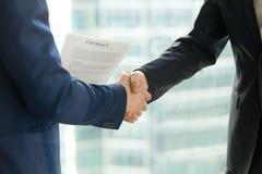 Χειραψία επιχειρηματιών, αρσενικό τίναγμα χεριών, που κρατά τη σύμβαση, γ Στοκ Εικόνες