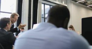 Χειραψία επιχειρηματιών μετά από να συζητήσει το νέο ξεκίνημα στο σύγχρονο coworking διάστημα ενώ οι επιχειρηματίες ομαδοποιούν τ φιλμ μικρού μήκους