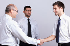 χειραψία τρία επιχειρηματιών υποδοχή Στοκ Φωτογραφία