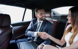 Χειραψία των επιχειρηματιών στη πίσω θέση ενός αυτοκινήτου Στοκ Εικόνα