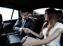 Χειραψία των επιχειρηματιών στη πίσω θέση ενός αυτοκινήτου Στοκ Εικόνες