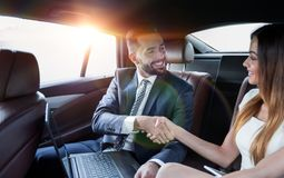 Χειραψία των επιχειρηματιών στη πίσω θέση ενός αυτοκινήτου Στοκ εικόνες με δικαίωμα ελεύθερης χρήσης