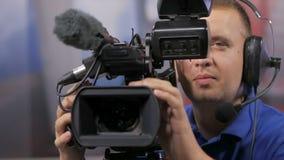 Χειριστής καμερών που εργάζεται με μια τηλεοπτική κάμερα ραδιοφωνικής μετάδοσης κινηματογράφων απόθεμα βίντεο