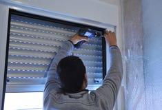 Χειριστής που εγκαθιστά ένα παράθυρο αργιλίου κατά τη διάρκεια της μεταρρύθμισης του σπιτιού στοκ φωτογραφία