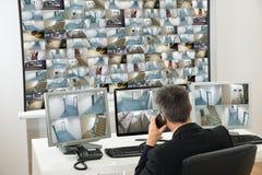 Χειριστής συστημάτων ασφαλείας που εξετάζει το μήκος σε πόδηα CCTV στοκ φωτογραφίες