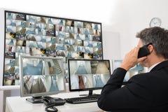 Χειριστής συστημάτων ασφαλείας που εξετάζει το μήκος σε πόδηα CCTV στοκ εικόνα