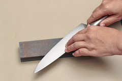 Χειριστείτε το μαχαίρι για να κάνετε ένα αιχμηρό μαχαίρι με μια ακόνη Στοκ φωτογραφία με δικαίωμα ελεύθερης χρήσης