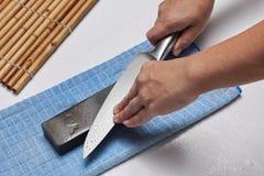 Χειριστείτε το μαχαίρι για να κάνετε ένα αιχμηρό μαχαίρι με μια ακόνη Στοκ Εικόνες