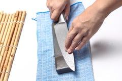 Χειριστείτε το μαχαίρι για να κάνετε ένα αιχμηρό μαχαίρι με μια ακόνη Στοκ Εικόνα
