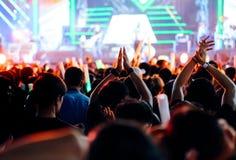 Χειροκρότημα ή χέρια πλήθους επάνω στα φω'τα σκηνών συναυλίας Στοκ Φωτογραφίες