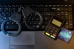 Χειροπέδες αστυνομίας χάλυβα, τραπεζικές κάρτες και συσκευή πληρωμής που βρίσκονται στο Κ Στοκ φωτογραφίες με δικαίωμα ελεύθερης χρήσης