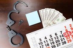 Χειροπέδες αστυνομίας χάλυβα, χρήματα δολαρίων και 15 Απριλίου στο ημερολόγιο, Στοκ Φωτογραφία