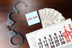 Χειροπέδες αστυνομίας χάλυβα, χρήματα δολαρίων και 15 Απριλίου στο ημερολόγιο, Στοκ φωτογραφίες με δικαίωμα ελεύθερης χρήσης