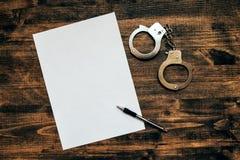 Χειροπέδες αστυνομίας και κενό έγγραφο για του ιδιωτικού αστυνομικού ανακριτών wor Στοκ φωτογραφία με δικαίωμα ελεύθερης χρήσης