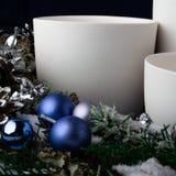 χειροποίητα άσπρα κεραμικά φλυτζάνια, στεφάνι του νέου έτους με τις διακοσμήσεις Χριστουγέννων στοκ φωτογραφία