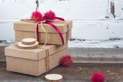 Χειροποίητα δώρα που τυλίγονται στο έγγραφο τεχνών για τον ξύλινο πίνακα Στοκ Φωτογραφία